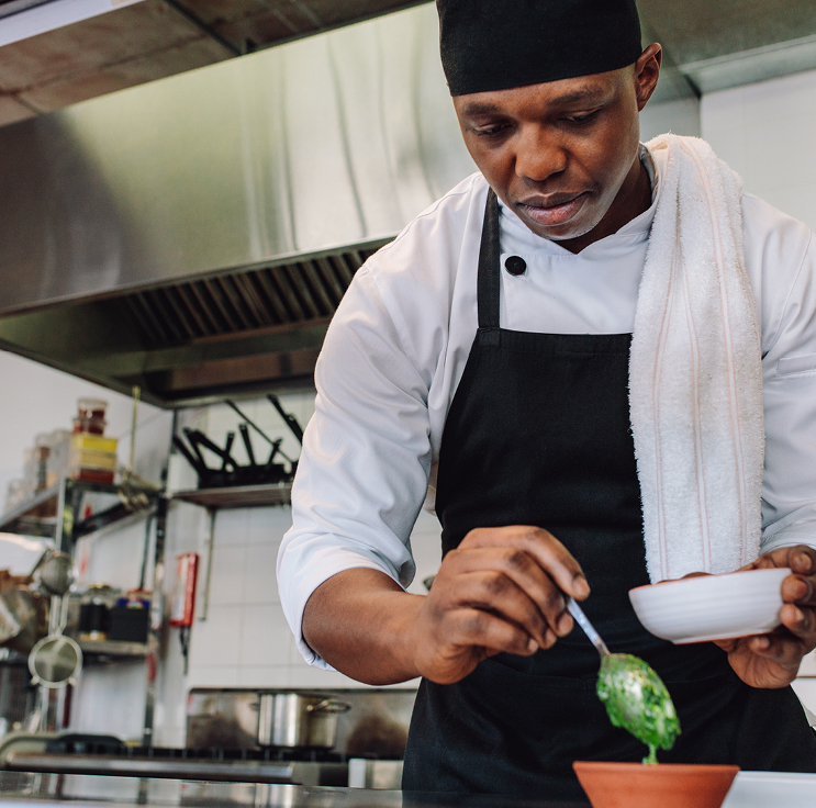 chef plating food in a high end commercial kitchen